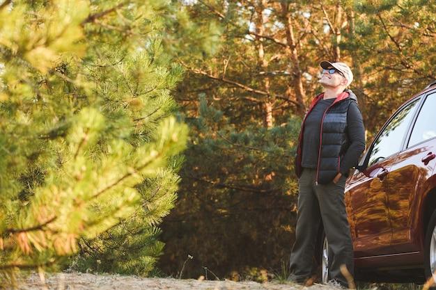 Szczęśliwy podróżnik w lesie iglastym, patrząc w górę