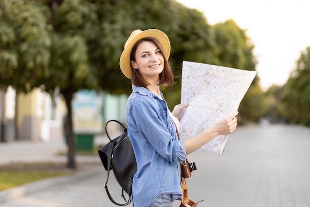 Szczęśliwy podróżnik z kapeluszową trzyma lokalną mapą
