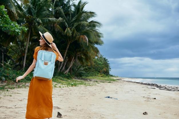 Szczęśliwy podróżnik z plecakiem na plecach idzie wzdłuż oceanu