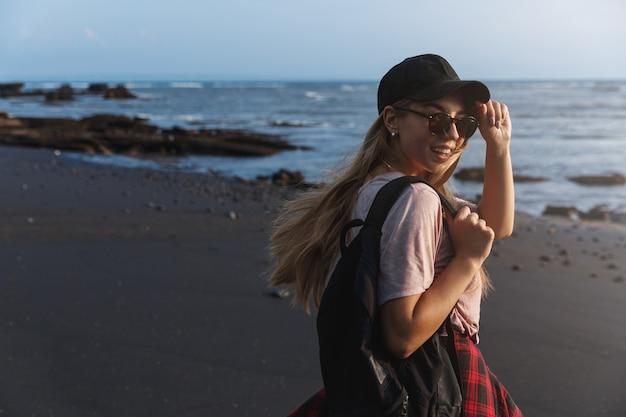Szczęśliwy podróżnik z plecakiem, odwraca się do aparatu z uśmiechem na plaży z czarnym piaskiem.