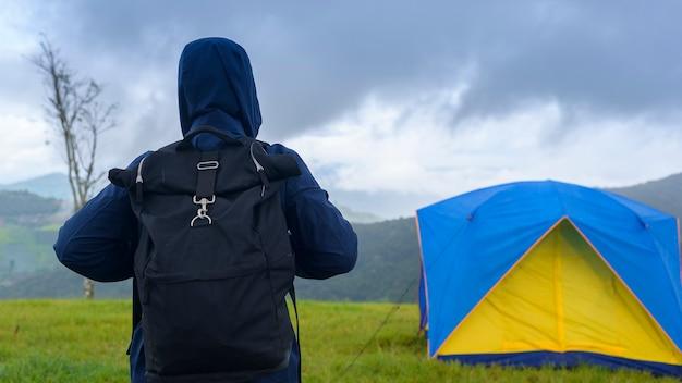 Szczęśliwy podróżujący człowiek korzystający i relaksujący w pobliżu namiotu obozowego