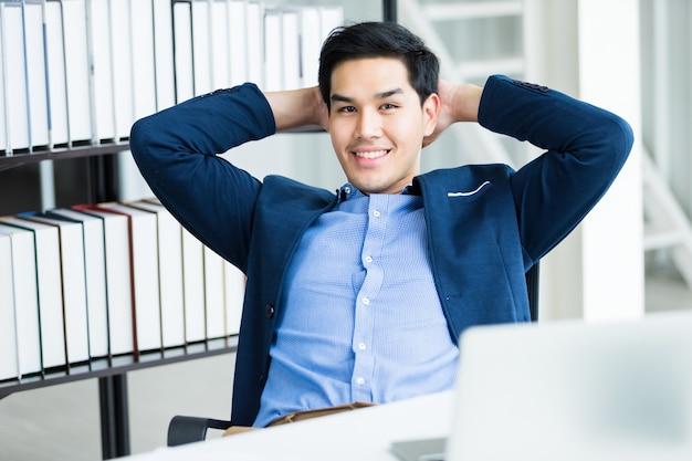 Szczęśliwy pomyślny azjatykci młody biznesmen na laptopie, pastylce z pustym dotyka ekranem odizolowywającym i piórze na notatniku na białym drewnianym stole w biurze