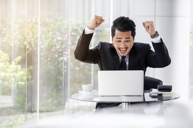 Szczęśliwy pomyślny biznesowy mężczyzna używa laptop