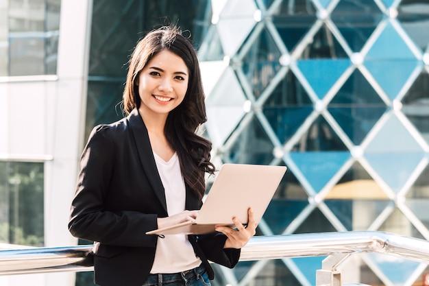 Szczęśliwy pomyślny bizneswoman używa laptop
