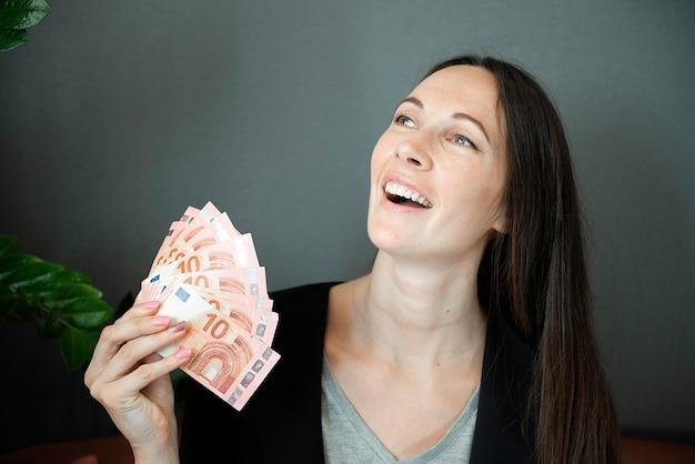 Szczęśliwy pomyślny młody biznes kobieta trzyma pieniądze euro rachunki w ręku na białym tle