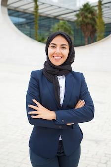 Szczęśliwy pomyślny muzułmański bizneswoman pozuje outside