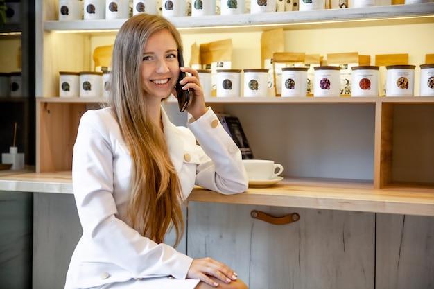 Szczęśliwy pomyślny uśmiechnięty bizneswomanu małego biznesu właściciel opowiada na telefonie