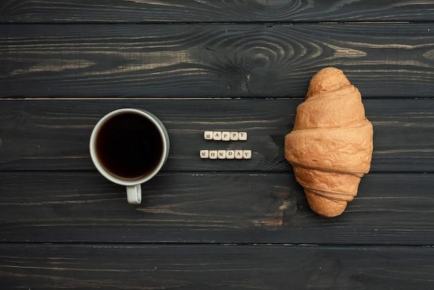 Szczęśliwy poniedziałek, wiadomość z rogalikiem i filiżanką kawy na ciemnym drewnianym stole