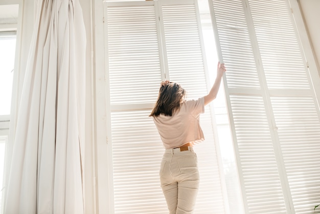 Szczęśliwy poranek młoda dziewczyna przy oknie hotelu, białe żaluzje, światło słoneczne