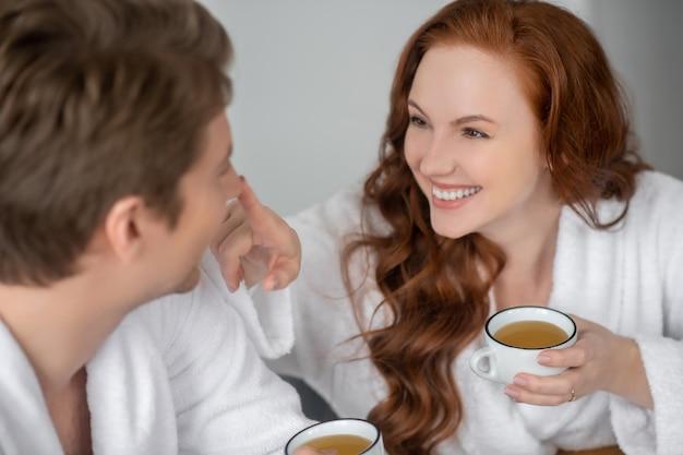 Szczęśliwy poranek. para w białych szlafrokach pije kawę i czuje się szczęśliwa?
