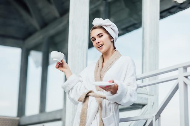 Szczęśliwy poranek. pojęcie piękna, uśmiechnięta dziewczyna ma czas na weekend i trzymając kubek z herbatą, miły poranek.