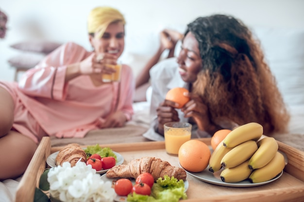 Szczęśliwy poranek. taca z lekkim zdrowym śniadaniem i kwiatami oraz dwiema szczęśliwymi dziewczynami w ubraniach do spania w tle
