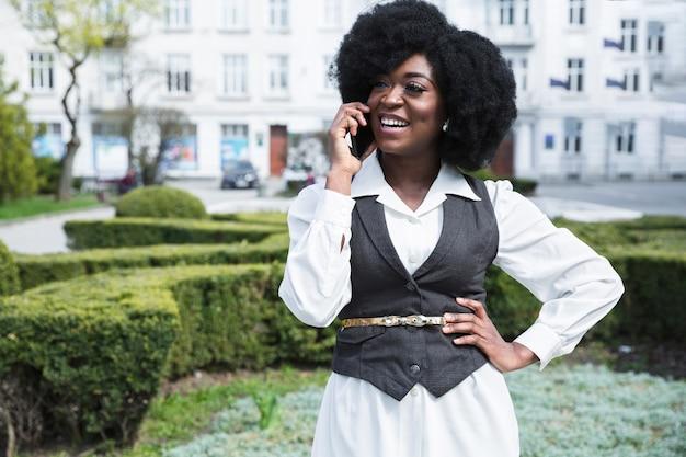 Szczęśliwy portret afrykański młody bizneswoman z jego ręką na biodrach opowiada na telefonie komórkowym