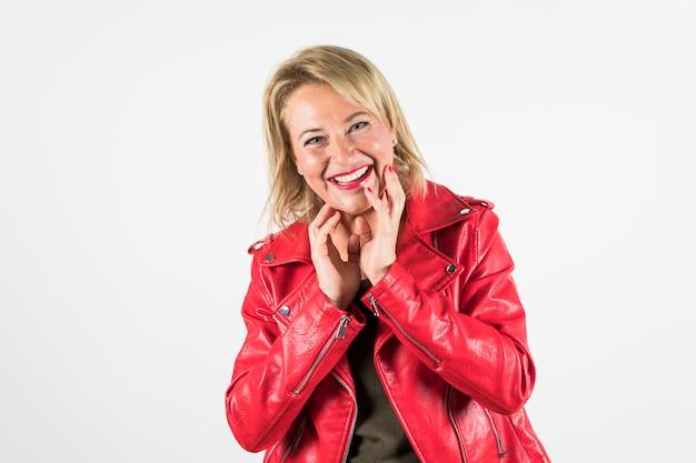 Szczęśliwy portret dojrzała kobieta w czerwonej kurtce odizolowywającej na białym tle
