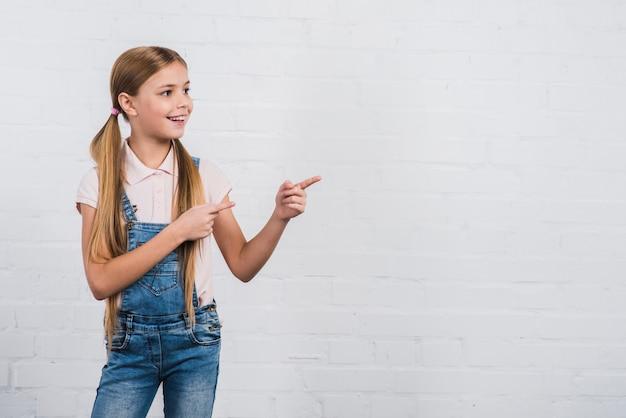 Szczęśliwy portret dziewczyna wskazuje palcową pozycję przeciw białemu ściana z cegieł patrzeje daleko od