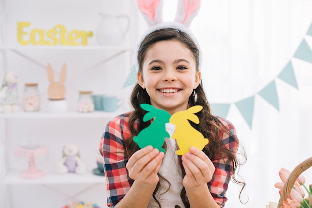 Szczęśliwy portret dziewczyny mienia koloru żółtego i zielonego papieru wycinanki królik na easter dniu