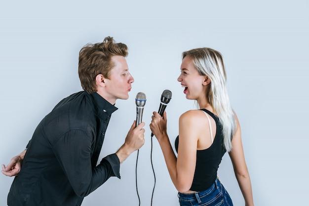 Szczęśliwy portret pary mienia mikrofon i śpiewa piosenkę