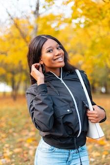 Szczęśliwy portret pięknej afro uśmiechniętej kobiety w czarnej casualowej kurtce z torebką spaceruje po parku z żółtymi jesiennymi liśćmi