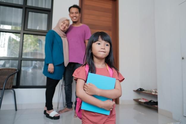 Szczęśliwy portret pięknej azjatyckiej uczennicy, która rano idzie do szkoły, podczas gdy rodzice są za nią