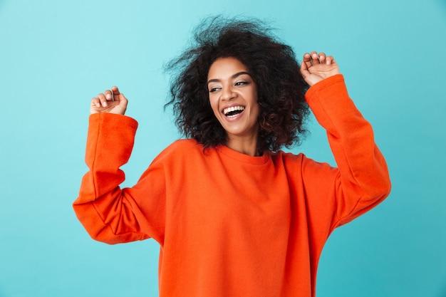 Szczęśliwy portret podekscytowanej kobiety w czerwonej koszuli, patrząc z uśmiechem i podnosząc ręce, na białym tle nad niebieską ścianą