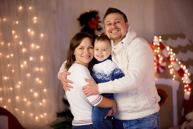 Szczęśliwy portret rodziny na boże narodzenie, matka, ojciec i dziecko w domu.