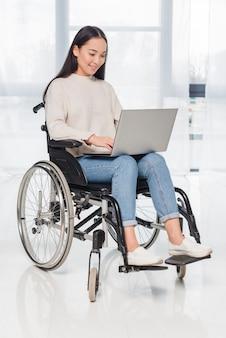 Szczęśliwy portret uśmiechnięta niepełnosprawna kobieta używa laptop