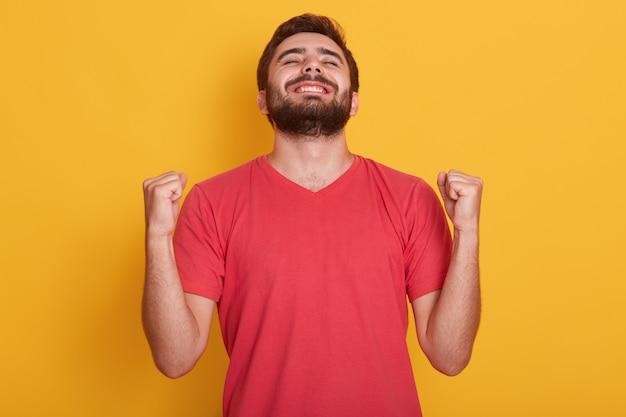 Szczęśliwy pozytywnie podekscytowany młody mężczyzna zaciskający pięści i krzyczący, ubrany w czerwoną swobodną koszulkę, mający dobre wieści, świętujący swoje zwycięstwo lub sukces, wygrywa na loterii. koncepcja emocje ludzi.