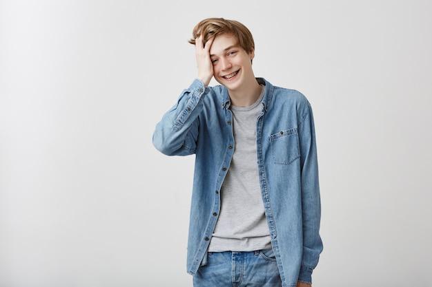 Szczęśliwy pozytywnie wyglądający model męski w dżinsowej koszuli i dżinsach, o jasnych włosach i niebieskich oczach, uśmiecha się szeroko, czuje się trochę nieśmiały, dotyka jego włosów. pojęcie piękna i młodości