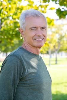 Szczęśliwy pozytywny dojrzały mężczyzna ubrany w sportową koszulkę z długim rękawem, stojący na zewnątrz i uśmiechnięty. sredni strzał. dojrzała sportowa osoba lub koncepcja aktywnego stylu życia