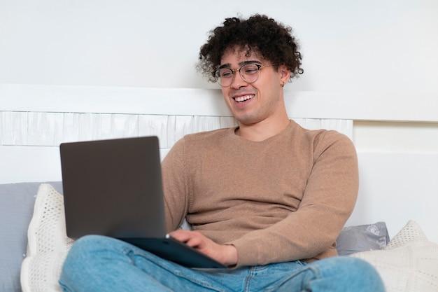 Szczęśliwy pozytywny facet młody wesoły radosny człowiek jest relaksujący, ciesząc się leżąc na łóżku przy użyciu swojego laptopa