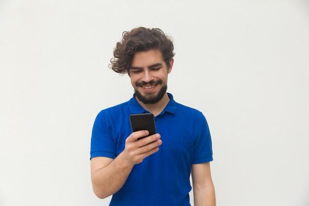 Szczęśliwy pozytywny facet używa telefon komórkowego