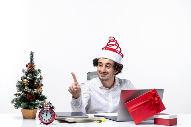 Szczęśliwy pozytywny młody biznesmen z śmieszne kapelusz świętego mikołaja mówi do kogoś w biurze na białym tle