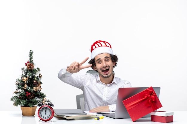 Szczęśliwy pozytywny młody biznesmen z śmieszne kapelusz świętego mikołaja, pokazując dwa w biurze na białym tle