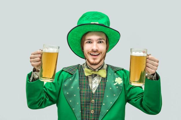 Szczęśliwy pozytywny młody człowiek w zielonym świętego patrick kostiumu trzyma dwa dużego kubka piwo i uśmiech