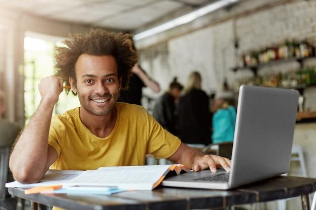 Szczęśliwy pozytywny student z afroamerykanów z radosnym, uroczym uśmiechem, korzystający z bezprzewodowego połączenia z internetem na laptopie w kawiarni, szukający informacji online do projektu badawczego