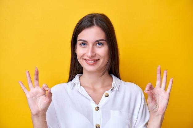 Szczęśliwy pozytywny uśmiechnięta brunetka dziewczyna pokazuje palce gest