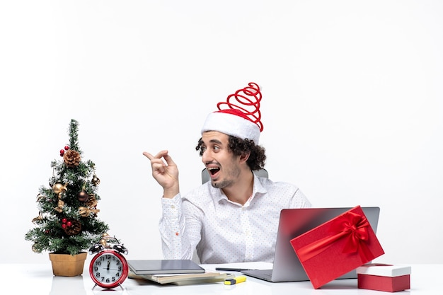Szczęśliwy pozytywny zaskoczony młody biznesmen z zabawnym kapeluszem świętego mikołaja mówi do kogoś w biurze na białym tle