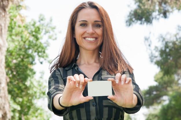 Szczęśliwy pozytywny żeński klient trzyma białą odznakę