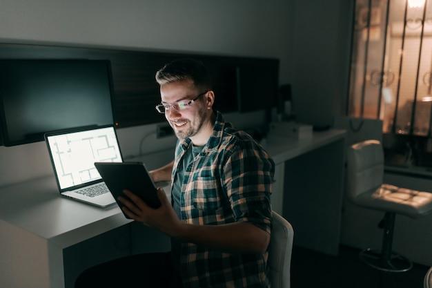 Szczęśliwy pracowity pracownik używa pastylkę i laptop podczas gdy siedzący w biurze póżno przy nocą