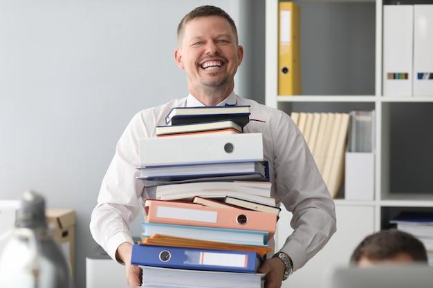 Szczęśliwy pracownik biurowy niesie ogromny ciężki stos papieru