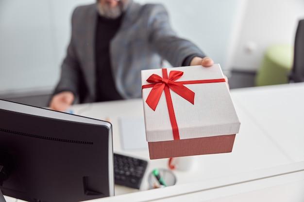 Szczęśliwy pracownik biurowy trzyma prezent i uśmiecha się