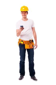 Szczęśliwy pracownik budowlany z mądrze telefonem