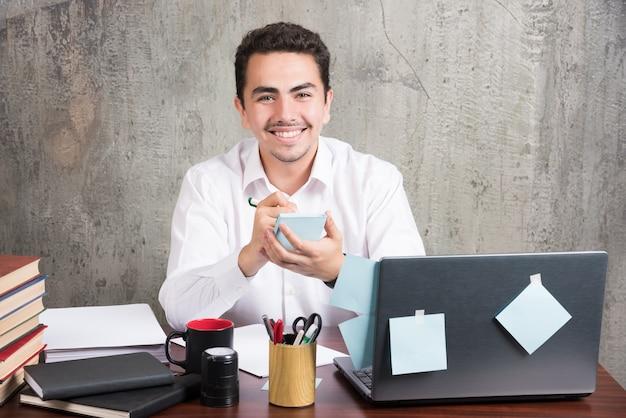 Szczęśliwy pracownik posiadający telefon przy biurku.