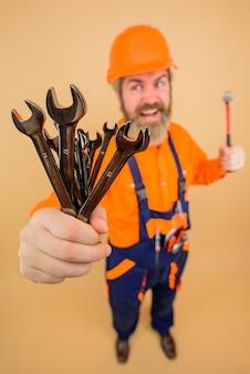 Szczęśliwy pracownik trzyma narzędzia naprawcze budowniczy budowniczy w budownictwie kask budowniczy mężczyzna twardy kapelusz