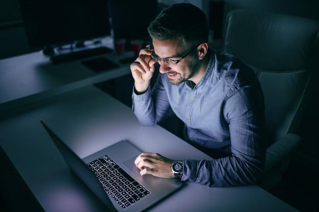 Szczęśliwy pracownik używa laptop dla pracować na projekcie podczas gdy siedzący w biurze póżno przy nocą.
