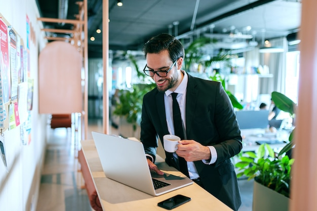 Szczęśliwy prawnik, odnoszący sukcesy, piszący e-mail na laptopie i pijący espresso, stojąc przy ladzie.