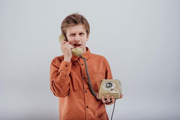 Szczęśliwy preteen rozmawiający na starym telefonie na białym tle