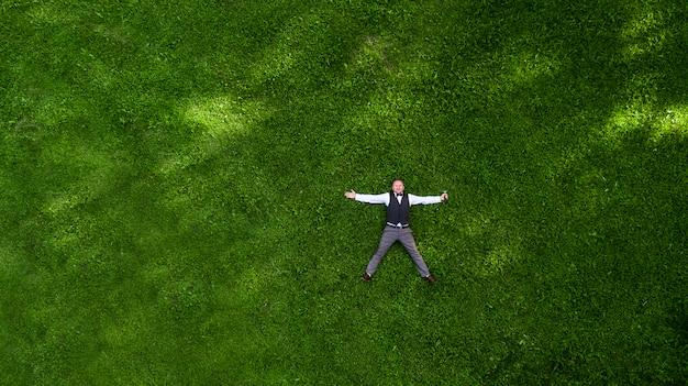 Szczęśliwy prezenter z mikrofonem na zielonym trawniku widok z góry fotografii lotniczej z dronem