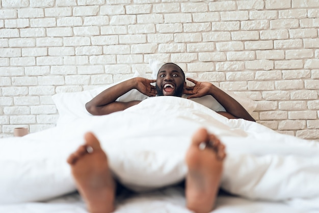 Szczęśliwy przebudzony mężczyzna jest wyciągnięty w łóżku. wcześnie rano.