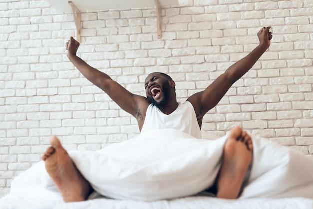 Szczęśliwy przebudzony mężczyzna jest wyciągnięty w łóżku.